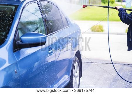 Manual Car Wash With Pressurized Water In Car Wash Outside.cleaning Car Using High Pressure Water.