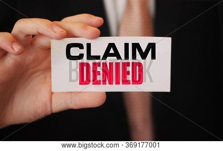 Businessman Shows A Card With Text Claim Denied . Injury Claim Insurance Concept
