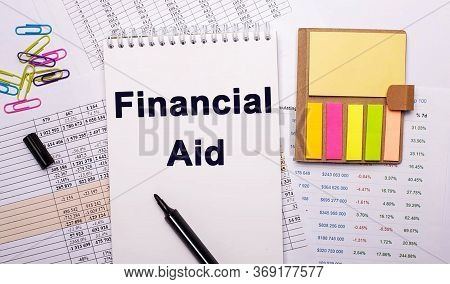 On A White Background Near Bright Papers Is Written Financial Aid. Financial Concept
