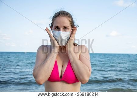 Concept Of Fear Of Disease While Traveling. Young Caucasian Girl In A Medical Mask And In A Swimsuit