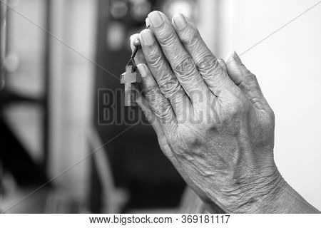 Clenched Hands Of The Elderly Woman With Jesus Christ Holy Cross Crucifix In Prayer Pose Gesture. On