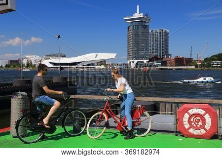 Amsterdam, Netherlands - July 9, 2017: Cyclists Wait For The Ferry To Cross Ij Bay In Amsterdam, Net