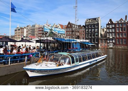 Amsterdam, Netherlands - July 9, 2017: People Wait For The City Tour Boat By Damrak Canal In Amsterd