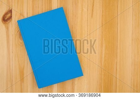 Blue Hardcover Book On Pine Wood Desk With Copy Space For Your School Or Reading Message Or Mockup