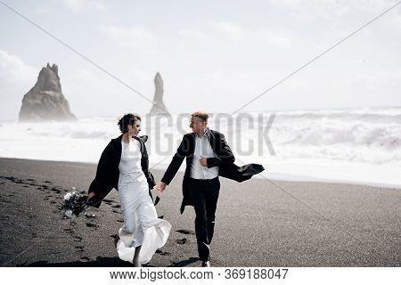 Destination Iceland Wedding. The Wedding Couple Runs Along The Sandy Black Beach Of Vik, Near The Ba