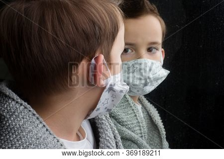 Boy Medical Face Mask, Looking Through The Glass, Laying A Hand On Him. The Concept Of Isolation And