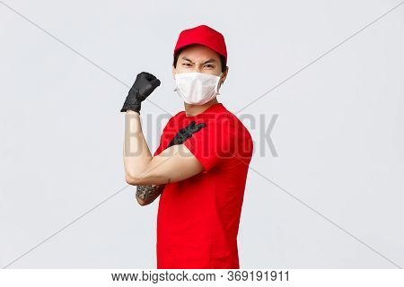 Strong Asian Guy Show-off His Strength, Carry Large Parcels At Work. Delivery Man In Uniform Flex Bi