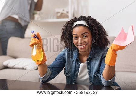 Smiling Black Housewife Holding Rag And Sprayer, Cleaning Table At Home While Her Boyfriend Wiping S