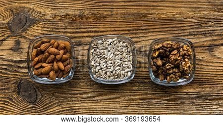 Almond, Walnut And Sunflower Seeds In A Small Plates Which Standing On A Wooden Vintage Table. Nuts