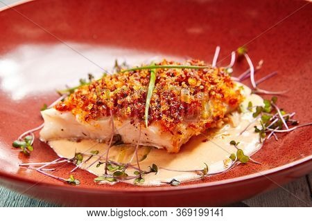 Cod piece with sauce in red deep plate. Fish cooked in tomato crumbs side view. Seafood dish in bowl close-up. Fancy restaurant dish. Art of cooking. Whitefish with batter garnish closeup