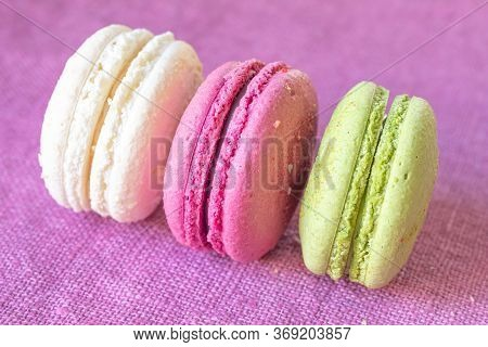 Multi-colored Macaroons On A Linen Napkin. Mcarons Or Macaroons Is French Or Italian Dessert. Close-