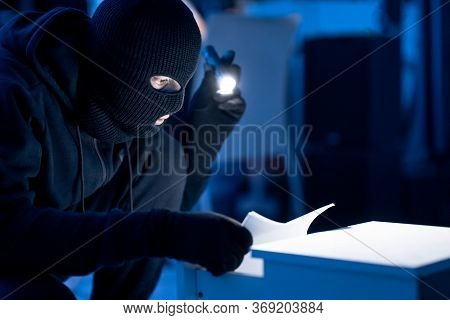 Industrial Espionage. Masked Intruder Holding And Reading Confidential Documents Using Flashlight At