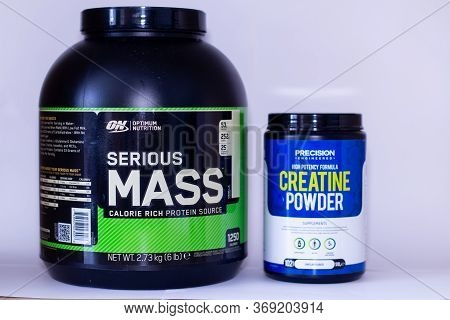 A Large Tub Of Bodybuilding Serious Mass Bulking Powder And A Smaller Tub Of Creatine Powder Against