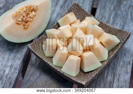 Sliced Cantaloupe In Wooden Plate On Old Table Background.