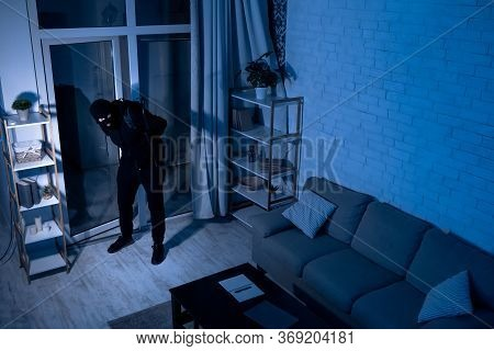 Housebreaking Concept. Intruder Sneaking Into House At Night, Holding Crowbar, Top View From Above C