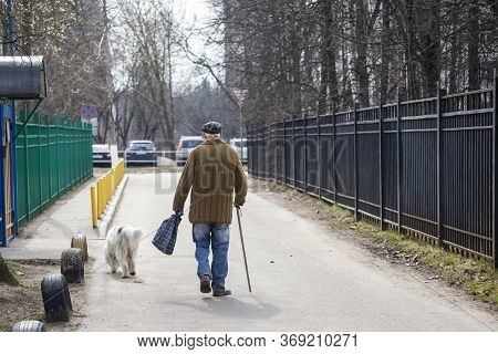 Grandfather Walks With A Dog. An Elderly Man Is Walking Along The Street With A Crutch. A Man Moves
