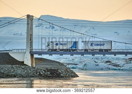 JOKULSARLON, ICELAND - MAY 2, 2018: Truck crossing the bridge over an icy lagoon. Eimskip is the oldest shipping company of Iceland.