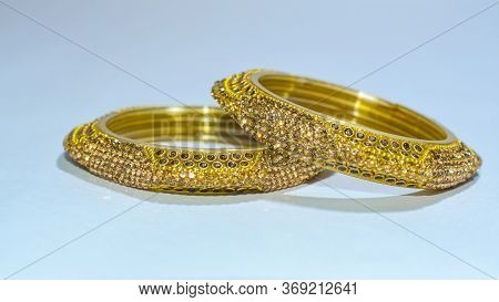 Golden Glass Metal Bangles With Stone Works On White Background.