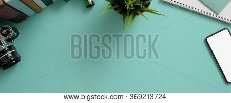 Creative Worktable With Mock-up Smartphone, Camera, Decoration, Books And Copy Space On Turquoise Ta