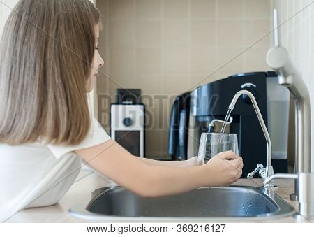 Child Pouring Fresh Reverse Osmosis Purified Water In Kitchen At Home. Drinking Tap Water. Consumpti