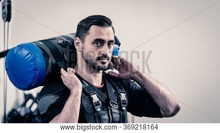 Portrait Of Handsome Fit Man In Electro Muscular Stimulation Vest Holding Heavy Leather Pad
