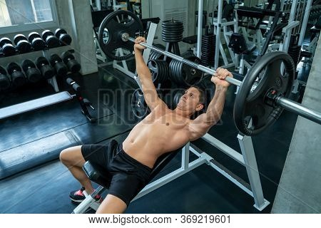 Muscular Man Working Out With Barbell Plate For Exercise In Fitness Gym.