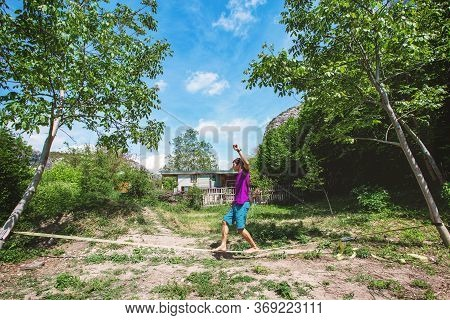 Man Walking On A Slack Line Outdoor In A Park, Summer Vacation Hobby.