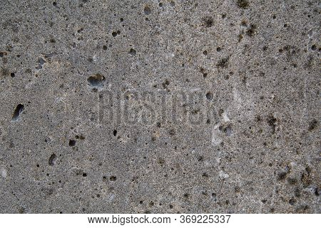 Texture Of An Aged And Weathered Grey Concrete Exterior Wall. Plenty Of Holes Around The Surface. Co