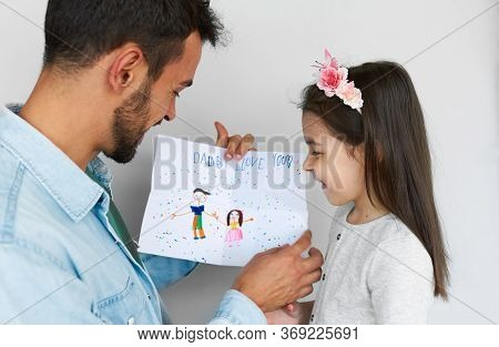 Closeup Image Of A Cute Daughter Giving A Greeting Card For His Smiling Father On Holiday For Father