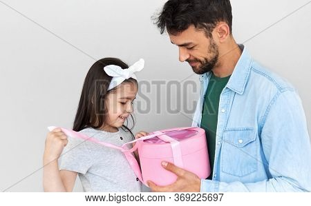Сute Daughter Giving To The Dad A Gift Box On Holiday For Father's Day. Pretty Little Girl Receives