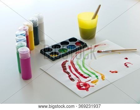White Paper With A Child's Drawing Made Of Colored Paint With Several Containers Of Tempera Paint An