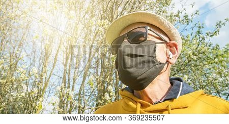 Pensioner In Sunglasses And Disposable Mask Wanders In Garden Listening To Music In Wireless Headpho