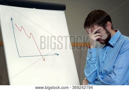 Frustrated Business Man Standing Near White Board In Office, Covers His Face With His Hand At The Fa