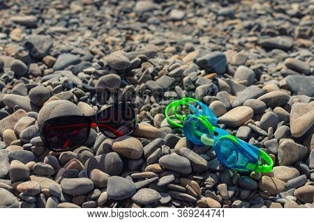 On The Seashore, Ochki For Swimming And Ochki Goggles From Sunlight Lie On The Stones. The Concept O