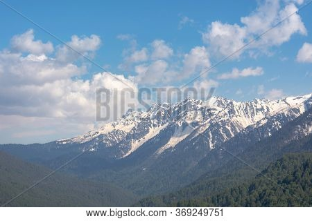 Snow-capped Mountains And Clouds. Spring Landscape With Mountains And Forest. Rosa Khutor Ski Resort
