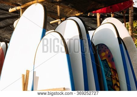 Close Up Set Of White Surfboard For Rent On The Beach In Sunshine. Multicolored Surf Boards Differen