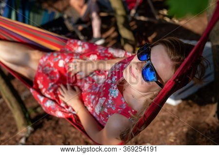 Outdoor Portrait Of Young Beautiful Blonde Cheerful Girl Enjoy In Hammock Outdoor. Relaxing In The H