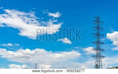 High Voltage Electric Pylon And Electrical Wire Against Blue Sky And White Clouds. Electricity Pylon