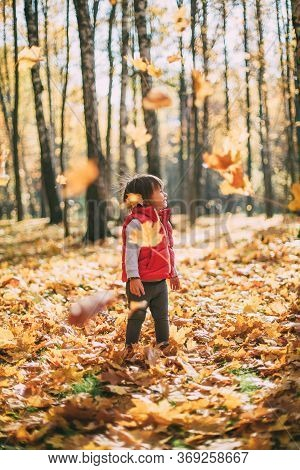 Little Beautiful Girl Loves Autumn, Walks In The Autumn Forest And Smiles