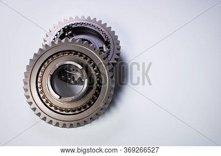 A Two New Gear Part On A Gray Background. The Concept Of New Parts And Spare Parts