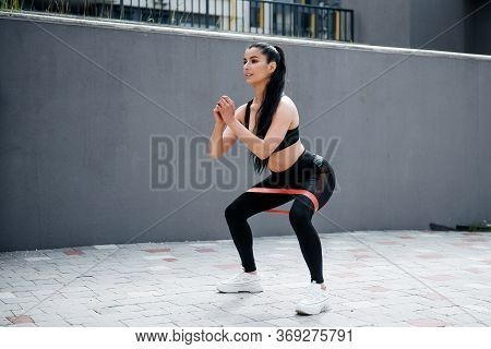 Young Sporty Fit Woman With Long Ponytail In Sportswear Squats With Fitness Elastic Band On Legs. Sp