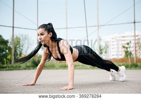 Attractive Woman Athlete Doing Plank Exercise On The Sports Field. Strong Brunette Woman In Sportswe