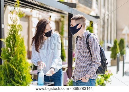 Happy Man And Woman Customers Disinfecting Hands Of A Female Guest At Outdoor Cafe. Trends Of Suppor