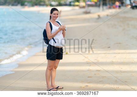 Pregnant woman walks along the beach