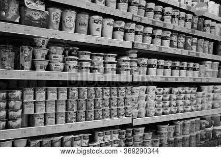 Black And White Image Of Variety Of Yogurt In Shelf In Shop. Greek, Plain, Flavored, Fruit Yogurt. I