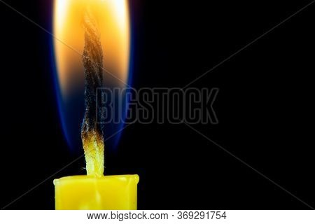 Church Wax Candle Burns On A Black Background