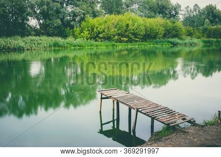 Pier On A Calm River In The Summer. Wooden Pier Bridge In The Morning. Place For Fishing In The Rive