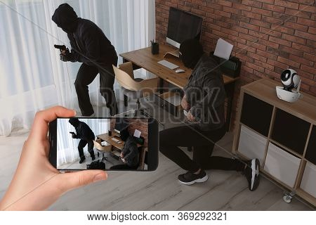 Man Monitoring Situation At His House With Cctv App On Smartphone, Closeup. Thieves Stealing Money
