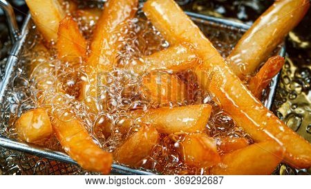 Cooking french fries in the deep fryer, crispy fries, Junk food concept