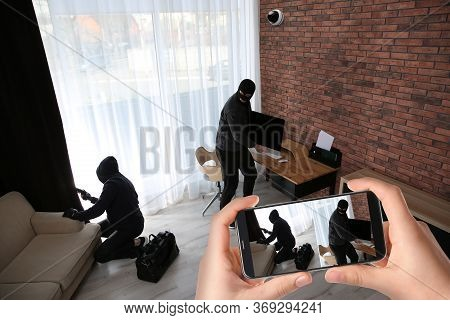 Man Monitoring Situation At His House With Cctv App On Smartphone, Closeup. Thieves Stealing Compute